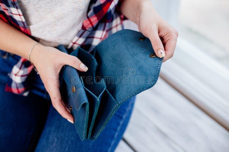 Ragazza che tiene un portafoglio blu dei soldi fotografia stock