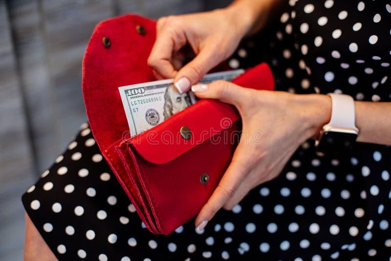 Ragazza che tiene un portafoglio rosso dei soldi fotografia stock libera da diritti