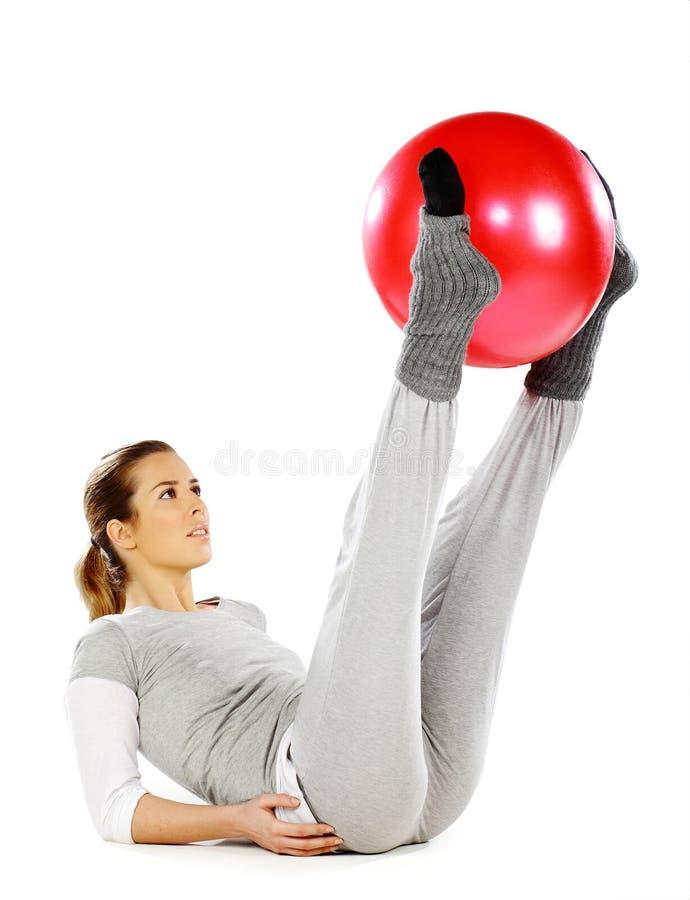 Ragazza che tiene una sfera rossa con i suoi piedini fotografie stock libere da diritti