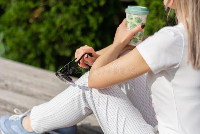 Ragazza che tiene una tazza di caffè e gli occhiali da sole in mani sulle gambe e che si siede sul banco in parco fotografia stock libera da diritti