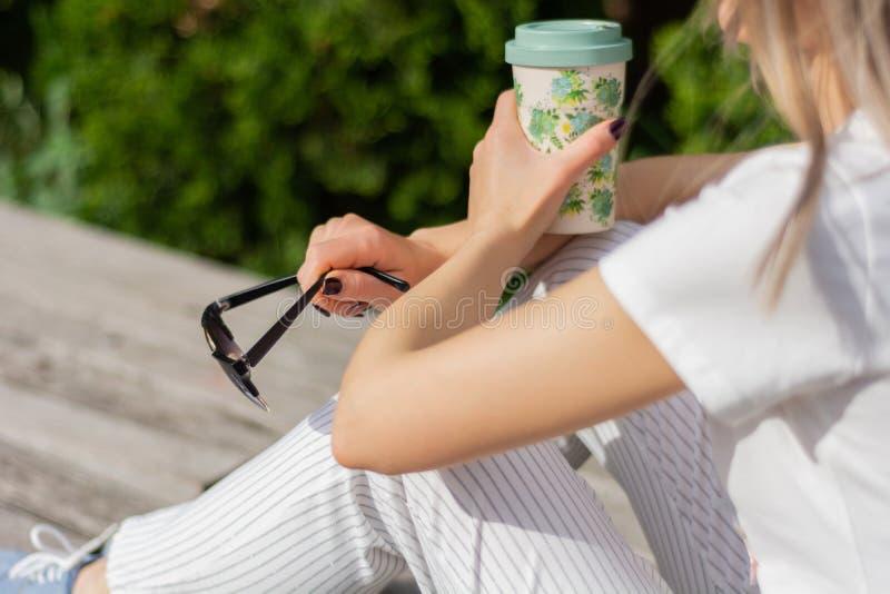 Ragazza che tiene una tazza di caff? e gli occhiali da sole in mani sulle gambe e che si siede sul banco in parco immagini stock