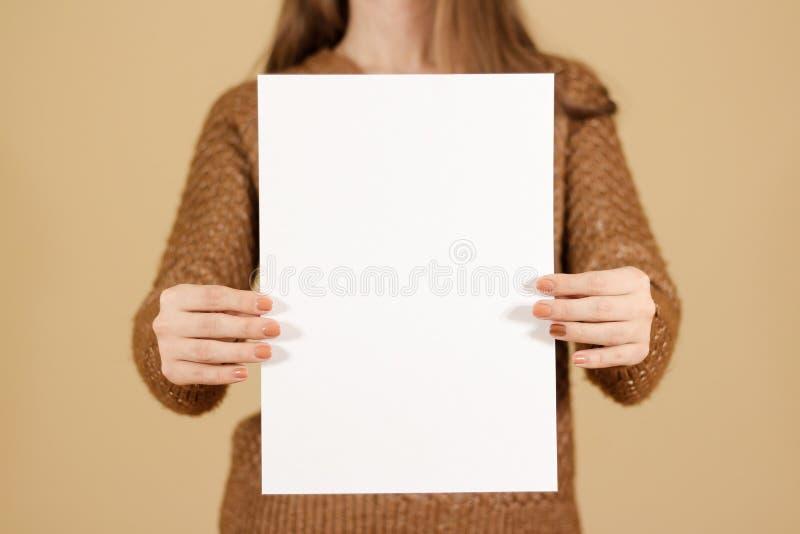 Ragazza che tiene verticalmente carta in bianco bianca A4 Presentati dell'opuscolo fotografia stock libera da diritti