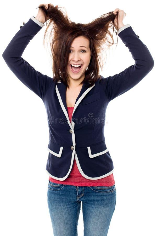 Ragazza che tira i suoi capelli nell'eccitazione fotografia stock libera da diritti
