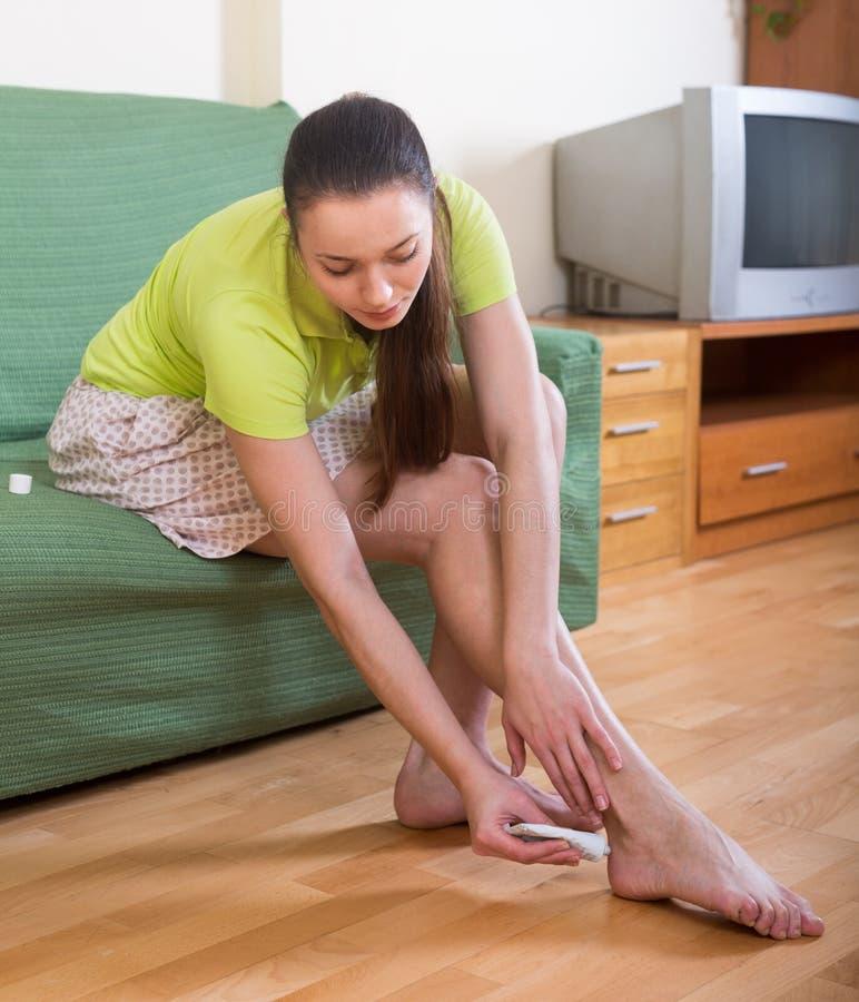 Ragazza che tratta i piedi con l'unguento fotografie stock libere da diritti