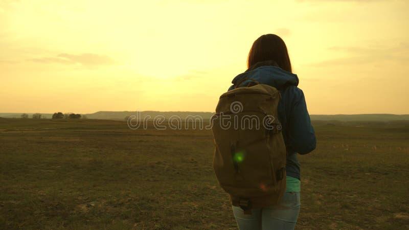 Ragazza che viaggiano con uno zaino contro il cielo ed il chiarore del sole la giovane donna turistica va su un tramonto al fotografie stock