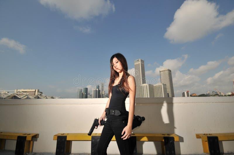 Ragazza cinese asiatica con la pistola che sembra fredda fotografie stock