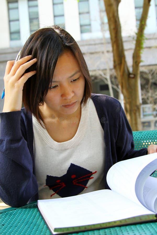 Ragazza cinese che è libri di lettura fotografia stock