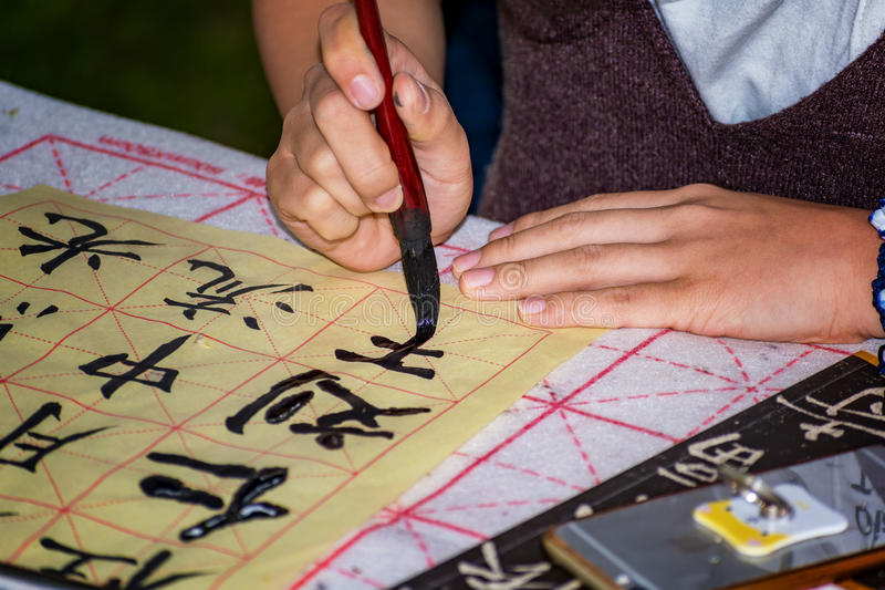 Ragazza cinese che fa esercizio di calligrafia fotografia stock