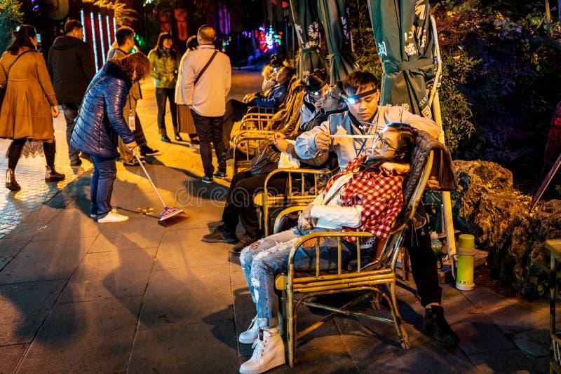Ragazza cinese che fa l'abitudine di pulizia dell'orecchio nella via antica di Jinli di Chengdu alla notte in Sichuan Cina immagini stock