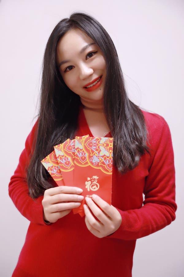 Ragazza cinese che tiene la tenuta rossa della donna dei pacchetti con soldi fortunati fotografie stock