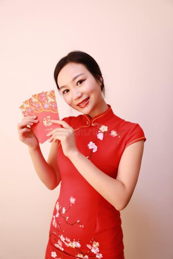 Ragazza cinese nel cheongsam tradizionale del vestito che tiene la tenuta rossa della donna dei pacchetti con soldi fortunati fotografie stock libere da diritti