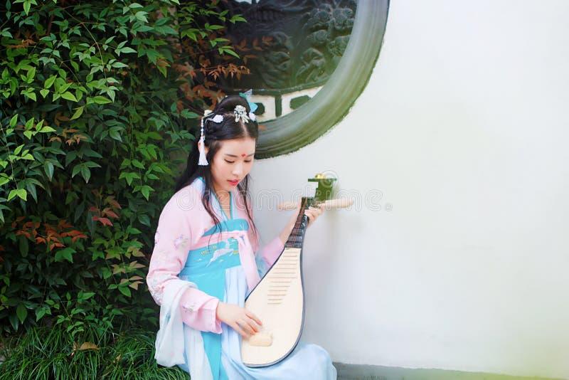 Ragazza cinese nel pipa antico tradizionale della chitarra della flauto del gioco di cosplay di hanfu del costume di dramma immagini stock
