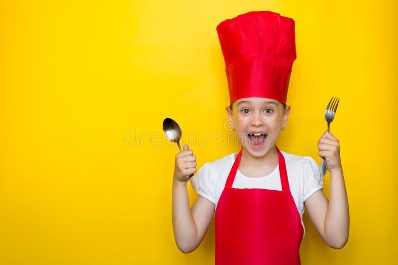Ragazza colpita e sorpresa che grida nel vestito di un cuoco unico rosso che tiene un cucchiaio e una forchetta su fondo giallo c immagini stock