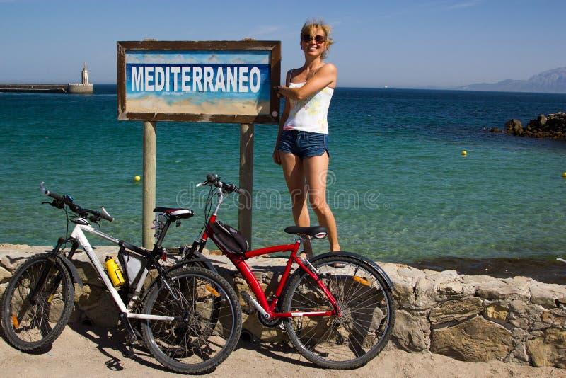 Ragazza con 2 biciclette contro il segno di Mediterraneo alla spiaggia Spagna immagine stock