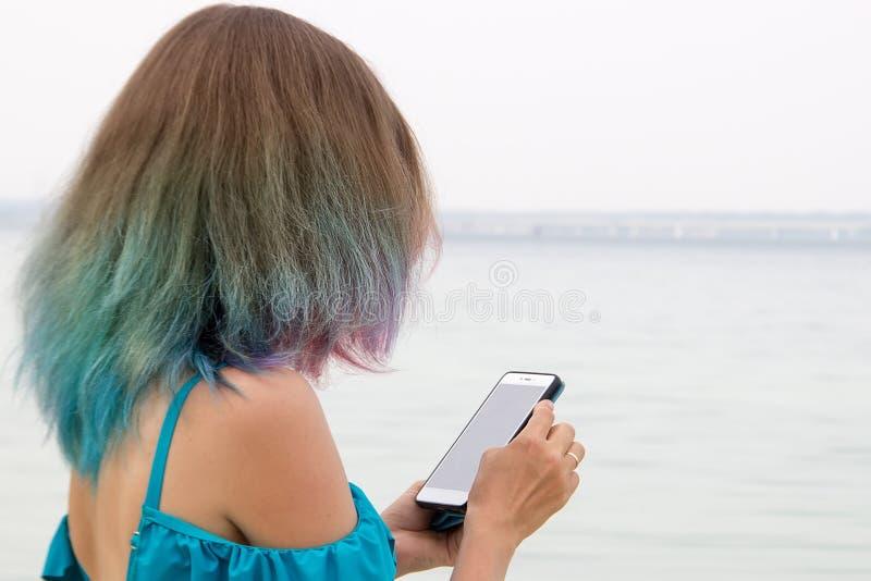 Ragazza con capelli colorati che esamina lo smartphone fotografie stock libere da diritti
