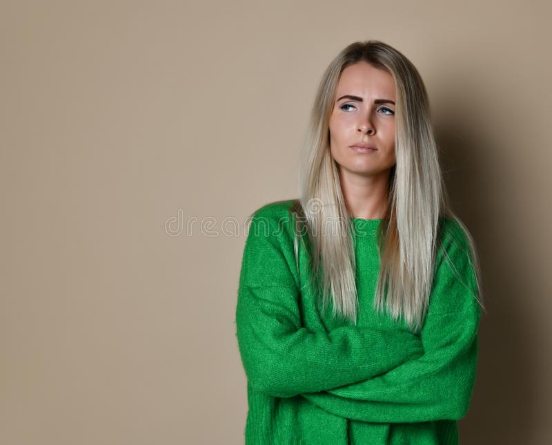 Ragazza con capelli diritti biondi che aggrotta le sopracciglia il suo fronte nel fastidio, maglione verde a maniche lunghe sciol immagini stock libere da diritti