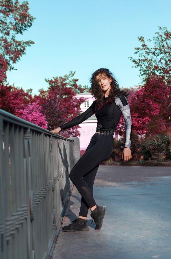 Ragazza con capelli ondulati in vestiti di sport sul ponte nel parco sui precedenti degli alberi porpora, bella donna fotografia stock libera da diritti