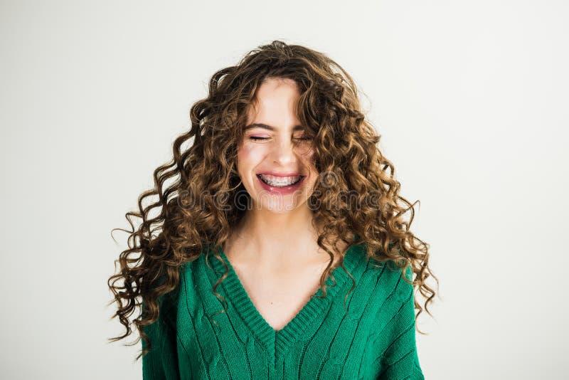 Ragazza con capelli ricci al parrucchiere alla parete bianca Ragazza parigina in vestiti di inverno Sguardo di modo e concetto di fotografia stock