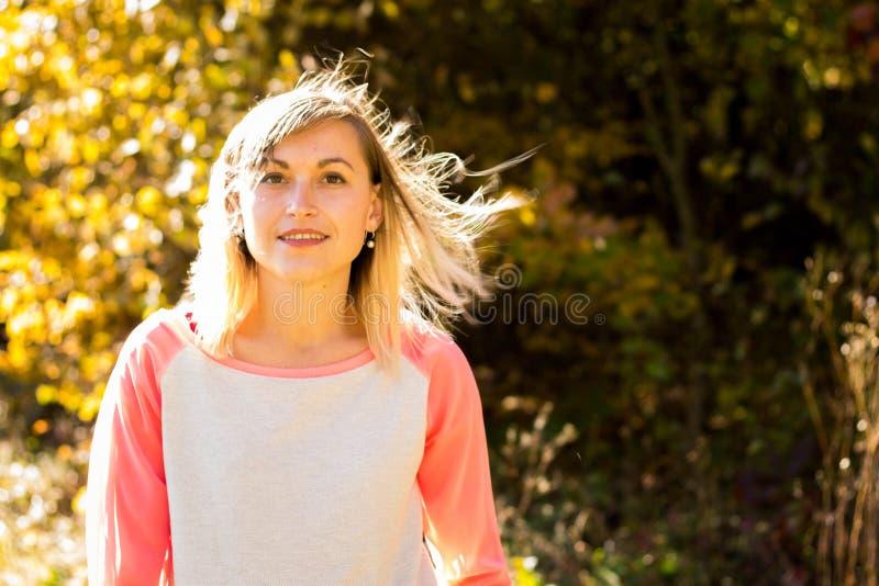 Ragazza con capelli sciolti sui precedenti degli alberi di autunno fotografia stock