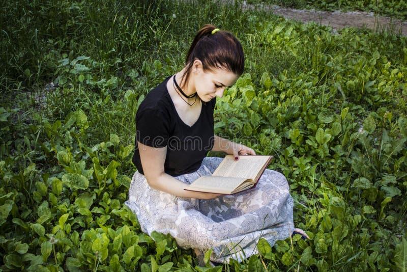 Ragazza con capelli scuri che si siedono sull'erba e che leggono un libro fotografie stock