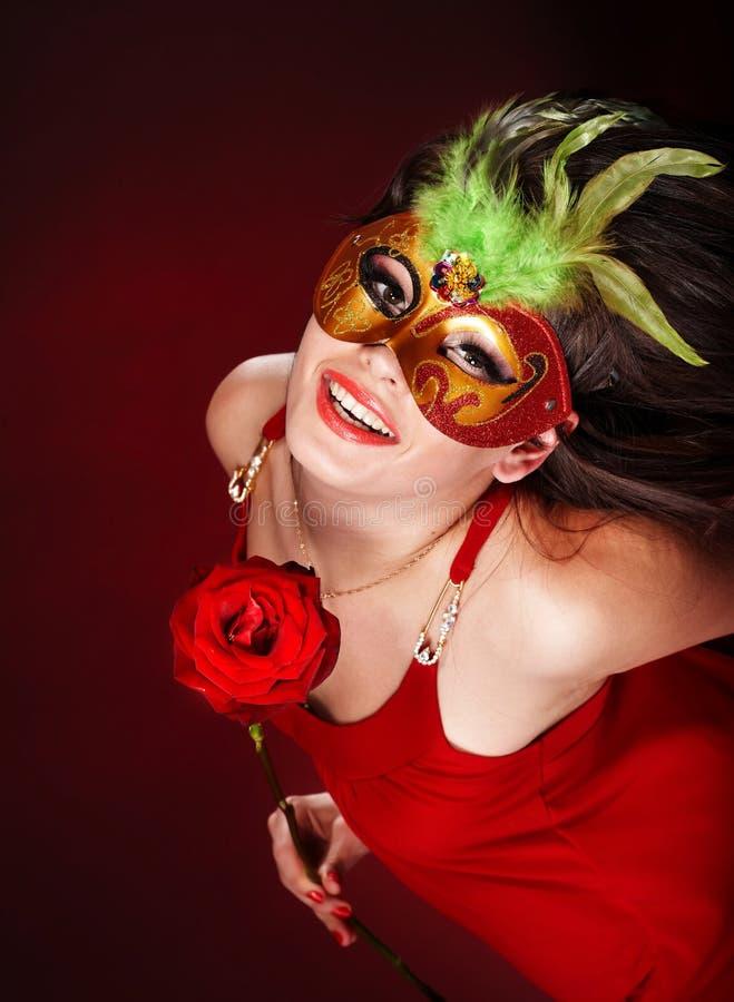 Ragazza con colore rosso di rosa e la mascherina. immagini stock