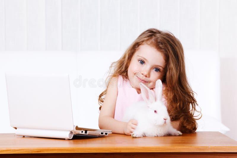 Ragazza con coniglio ed il computer portatile bianchi immagine stock