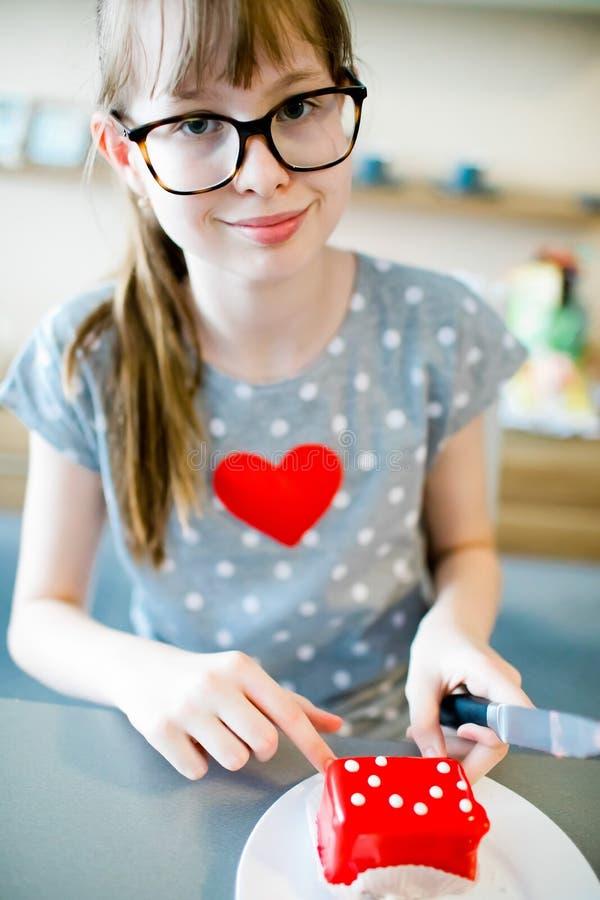 Ragazza con cuore sulla maglietta e sul coltello a disposizione che vanno affettare dolce rosso immagini stock libere da diritti
