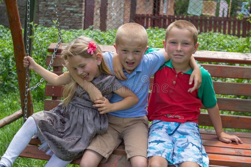 Ragazza con due fratelli, riunione dei bambini del ` dei compagni di classe sull'abbraccio del banco fotografia stock