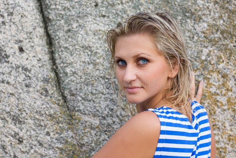 Ragazza con gli occhi azzurri sui precedenti delle rocce fotografia stock libera da diritti