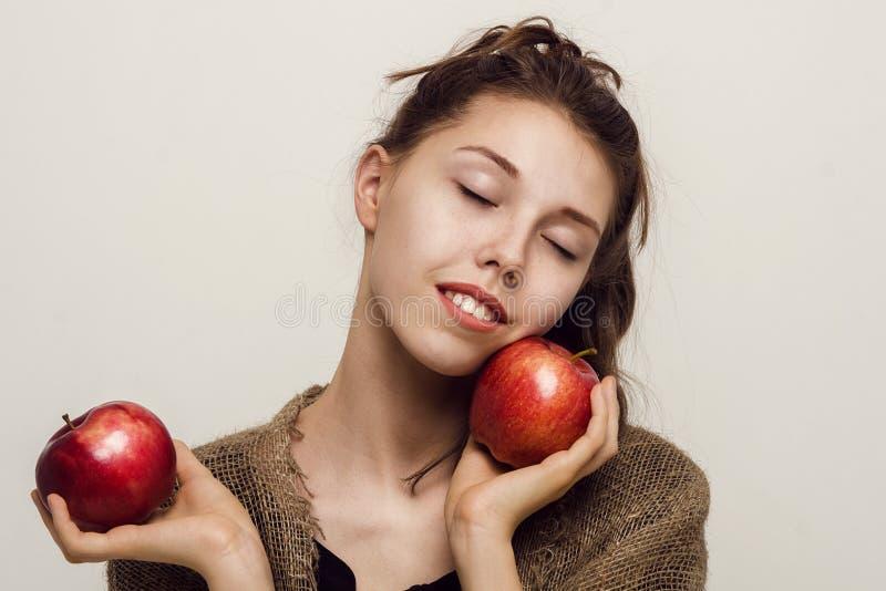 Ragazza con gli occhi chiusi e le mele rosse, foto dello studio, ritratto del primo piano fotografie stock