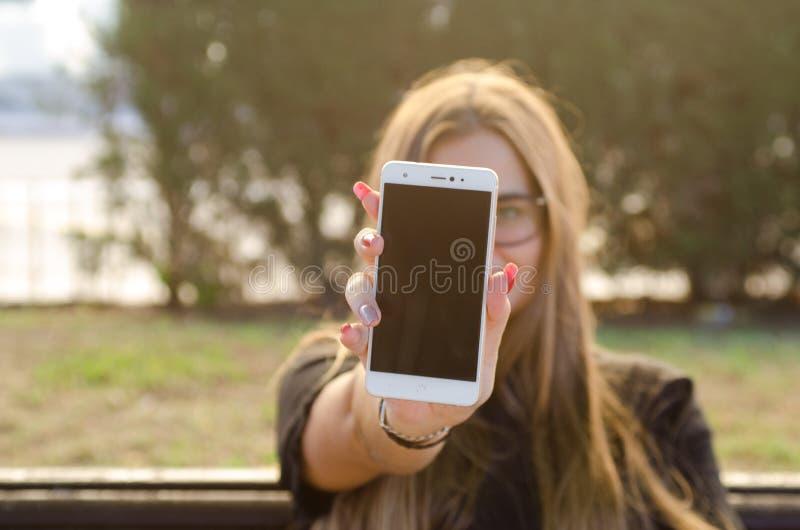 Ragazza con i chiodi rossi, mostranti smartphone bianco con lo schermo nero fotografia stock