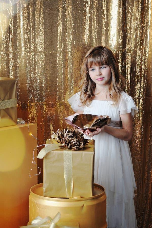Ragazza con i contenitori di regalo dell'oro sul compleanno fotografie stock