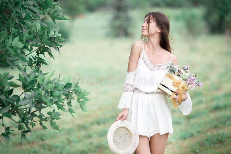 Ragazza con i fiori in cappello di estate che posa sul campo immagine stock libera da diritti