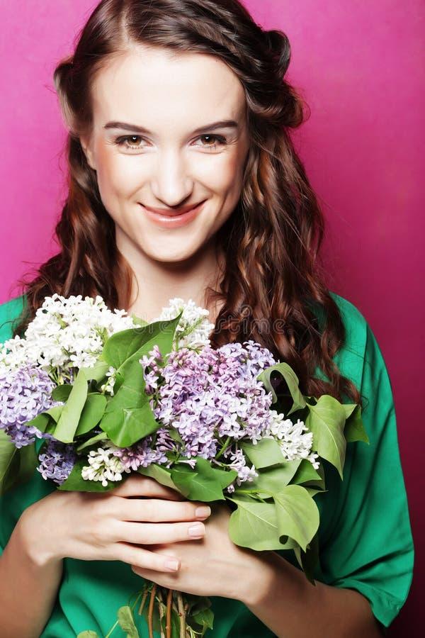 Ragazza con i fiori lilla sopra fondo rosa fotografie stock