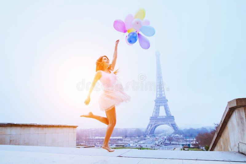 Ragazza con i palloni che saltano vicino alla torre Eiffel a Parigi fotografia stock libera da diritti