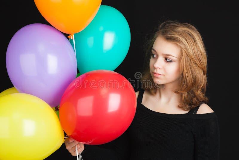 Ragazza con i palloni variopinti sopra fondo nero immagini stock libere da diritti