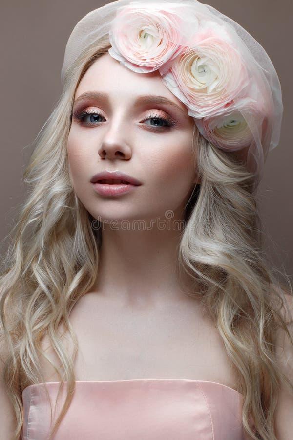 Ragazza con i riccioli in un cappello con il velo Bello modello con una corona dei fiori su lei capa immagine stock
