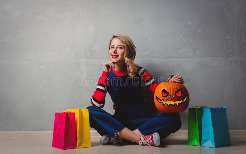 Ragazza con i sacchetti della spesa e la zucca di Halloween fotografia stock
