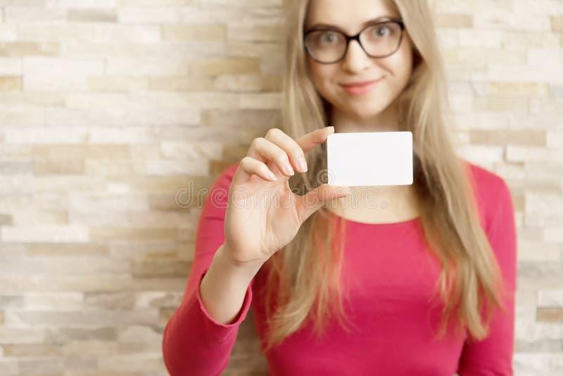 Ragazza con i vetri che mostrano biglietto da visita in bianco fotografia stock