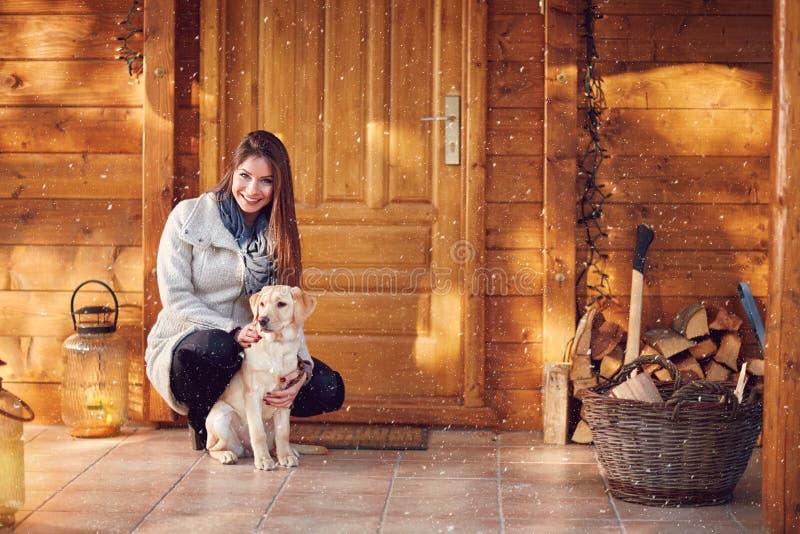 Ragazza con il cane davanti alla casa di legno immagine stock