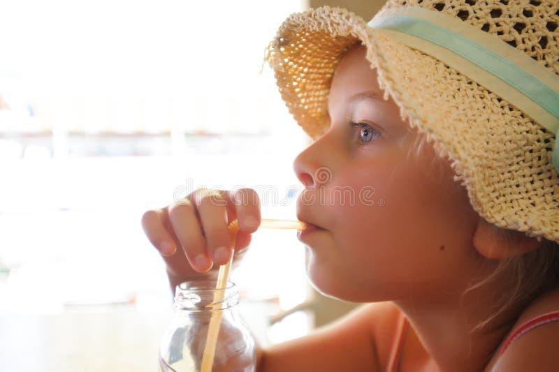 Ragazza con il cappello che beve con la paglia immagine stock libera da diritti