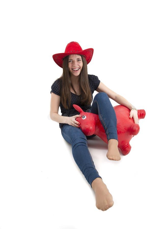 Ragazza con il cappello da cowboy rosso che monta il cavallo del giocattolo della o immagine stock libera da diritti