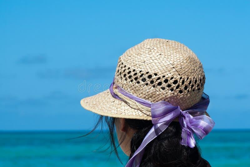 Ragazza con il cappello di paglia alla spiaggia fotografie stock