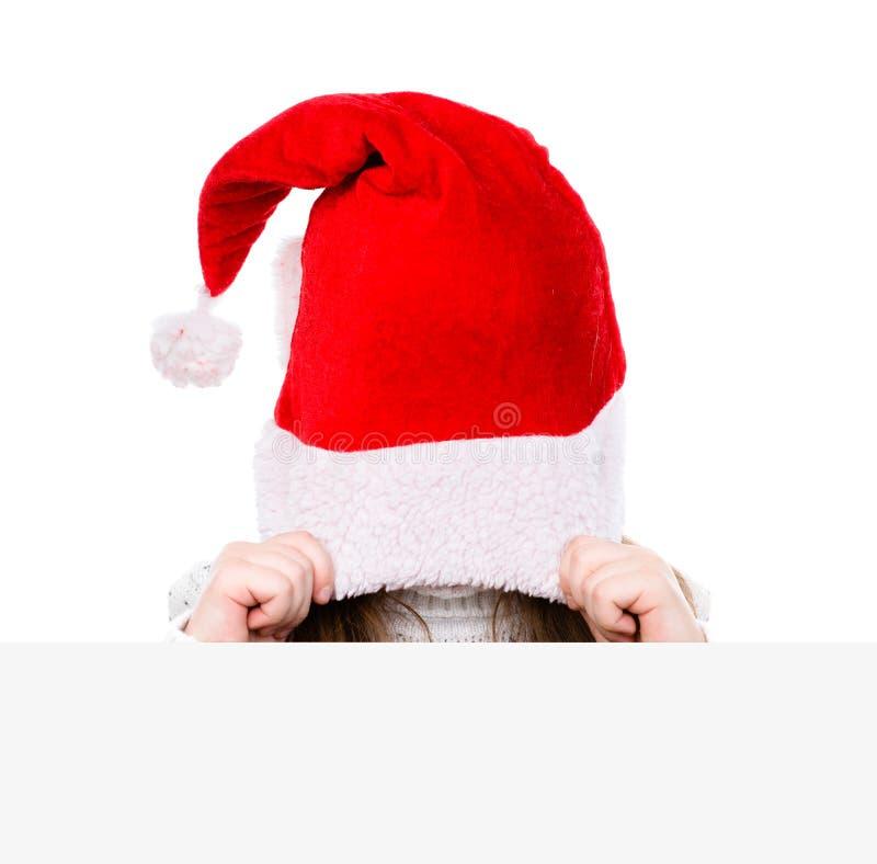 Ragazza con il cappello rosso di Santa che dà una occhiata dietro un bordo in bianco O isolata fotografia stock