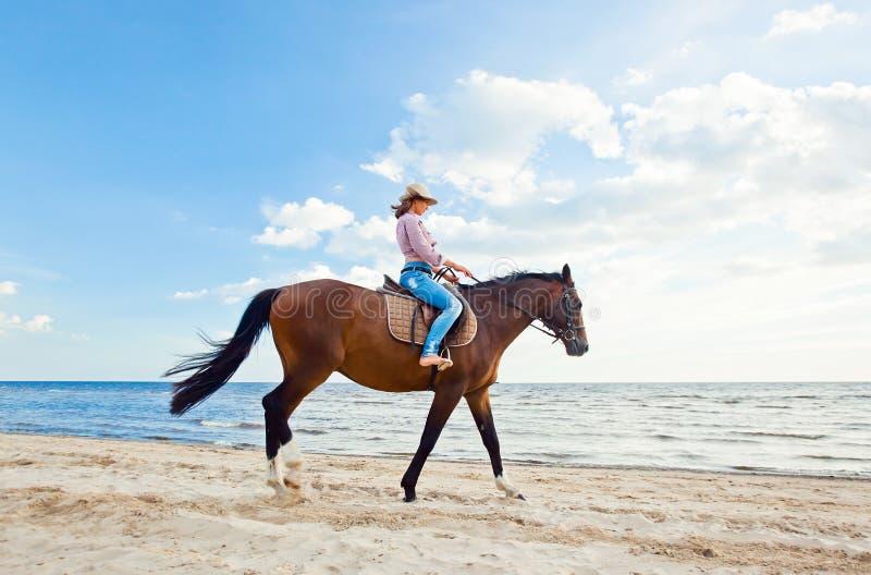 Ragazza con il cavallo sul litorale immagini stock
