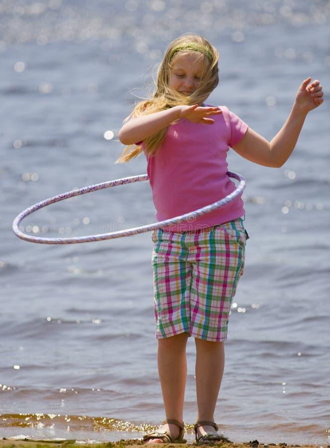 Ragazza con il cerchio di Hula sulla spiaggia fotografia stock