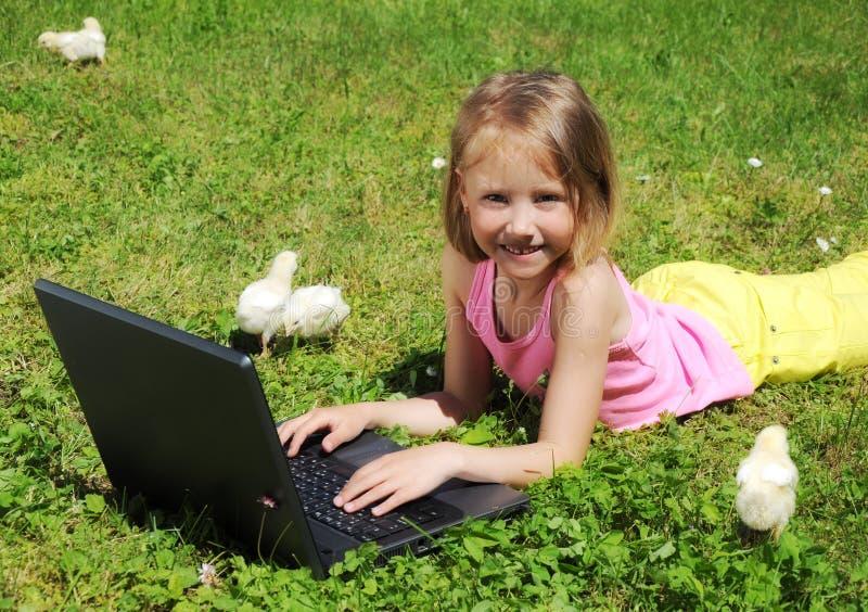 ragazza con il computer portatile che pone sull'erba verde fotografia stock