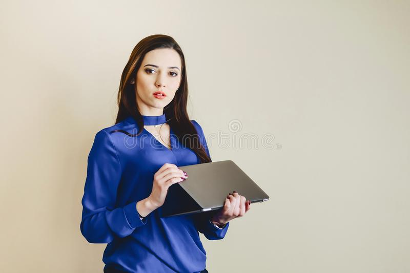ragazza con il computer portatile su fondo della parete fotografia stock