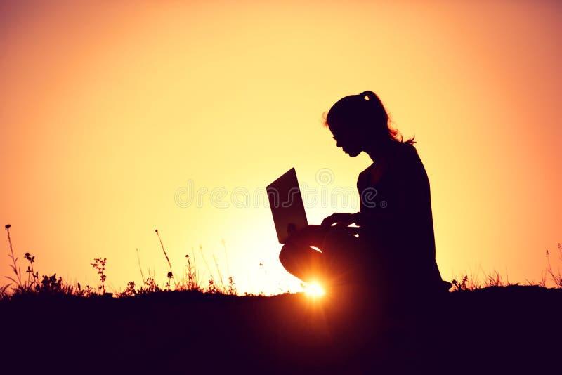 Ragazza con il computer portatile sul tramonto fotografie stock libere da diritti