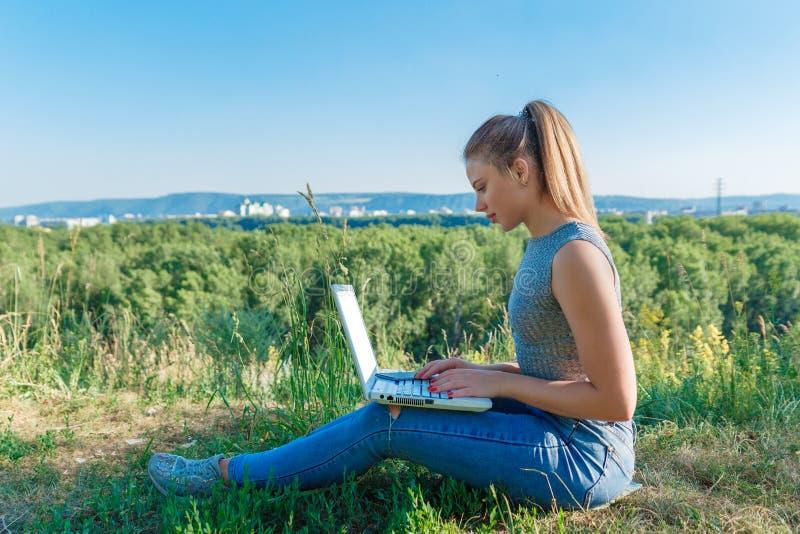 Ragazza con il computer portatile sulla natura sui precedenti della foresta e del cielo Il concetto di combinazione svago e del l immagini stock